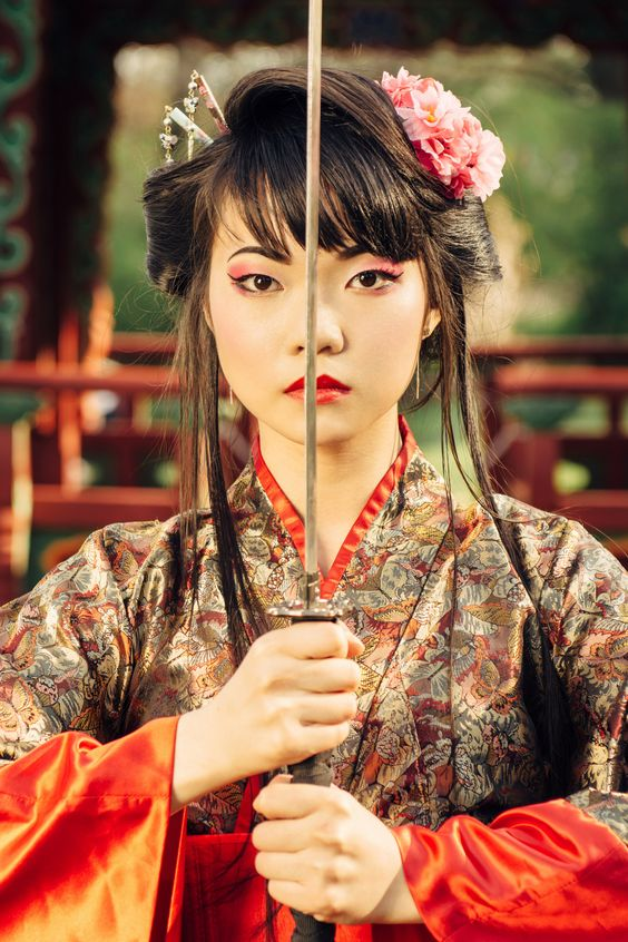 Beautiful korean woman or  geisha in kimono holding samurai sword near face